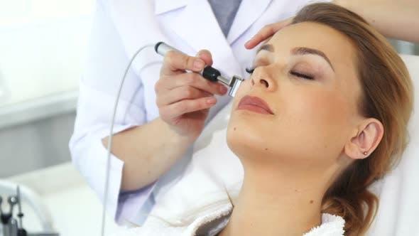 Thumbnail for Kosmetikerin verwendet Iontophorese Roller für das Gesicht des Kunden