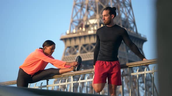 Thumbnail for A couple stretching before running across a bridge with the Eiffel Tower