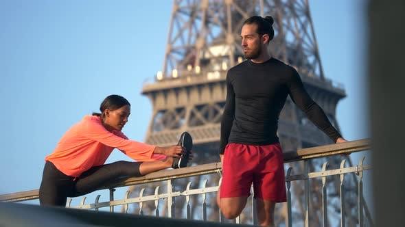Thumbnail for Ein Paar, das sich vor dem Lauf über eine Brücke mit dem Eiffelturm erstreckt