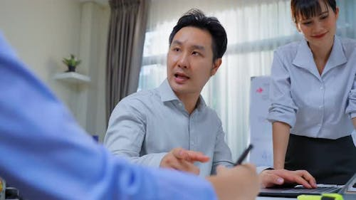 Asian business man work on computer for business project, follow direction from leader in office.