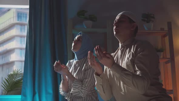 Portrait Muslim Man and Woman in Hijab Pray at Home