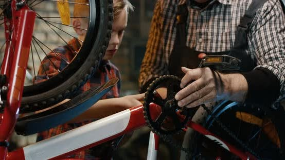 Thumbnail for Grandfather and Grandson Repairing a Bicycle in a Garage