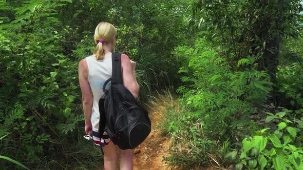 Thumbnail for tourist girl is traveling along a tropical island. walking through the rainforest