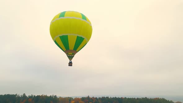 Aerial Drone View of Balloon Flight on a Cloudy Day. A Balloon Flying Low Above the Ground. Autumn