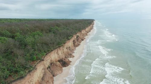 Aerial View of Ocean Waves Beating Against a Rocky Shore on a Wooded Tropical Seaboard