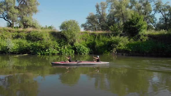 Thumbnail for An Aerial View. A Man and a Woman Swim on a Kayak on a River.