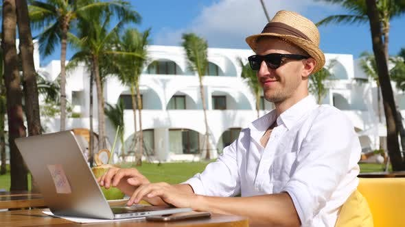 Digital Nomad Man In Hat Working Remotely On Laptop On Beach
