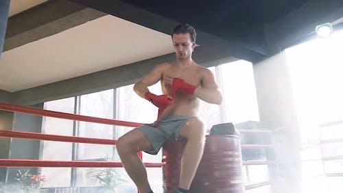 Junger Mann Boxer wickelt rote Bandagen in der Turnhalle