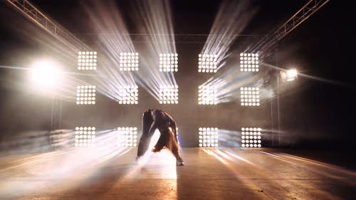 Talented Female Dancer on Stage with Spotlight on the Wall