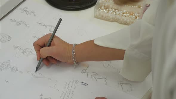 Thumbnail for Overhead View Looking Down Jewelry Designer in Studio Sketching Out Designs
