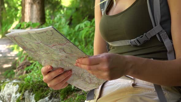 Thumbnail for A Woman Reads a Map in a Forest - Closeup
