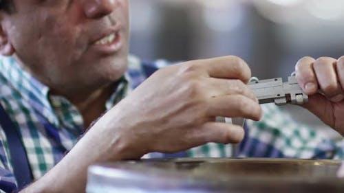 Hispanic Laborer Using Caliper
