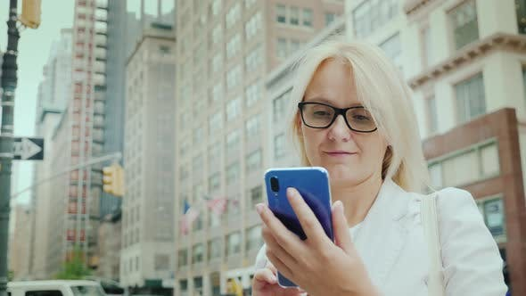 Thumbnail for Businesswoman Uses Smartphone on Manhattan in New York