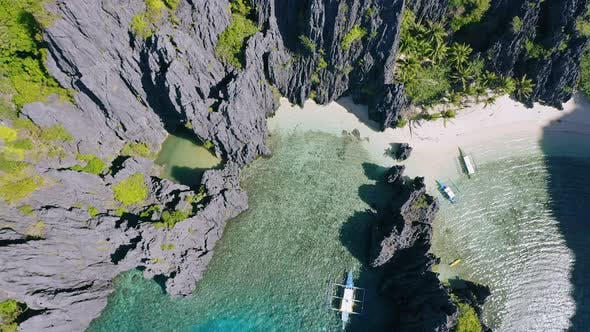 Thumbnail for Top Down Aerial Footage of Tourist Boats Moored Between Karst Cliffs at Secret Lagoon Beach in