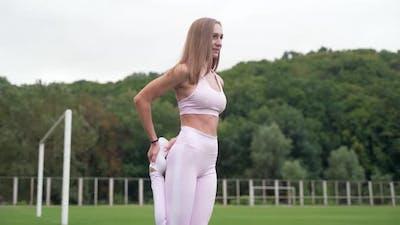 Beautiful woman doing warm-ups outdoors