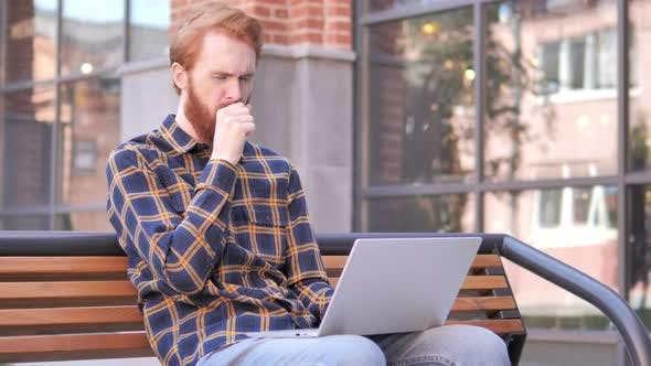 Thumbnail for Redhead Beard Young Man Coughing while Working on Laptop Outdoor