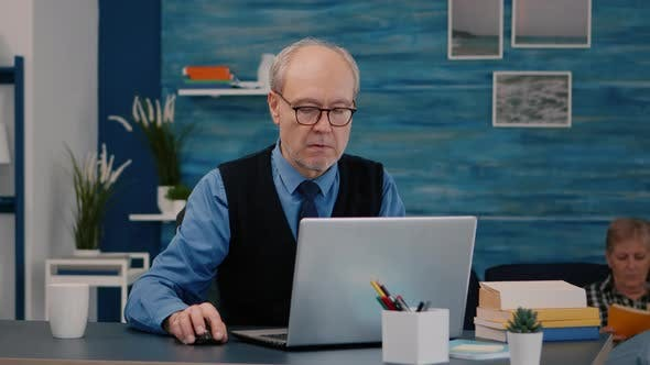 Senior Businessman Reading Reports Sitting in Front of Laptop