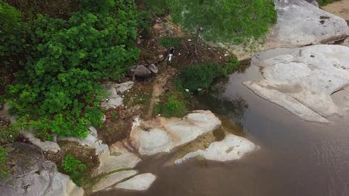 Aerial Shot of a Motocross Rider Driving a Dirt Bike in the Rough Path the River.