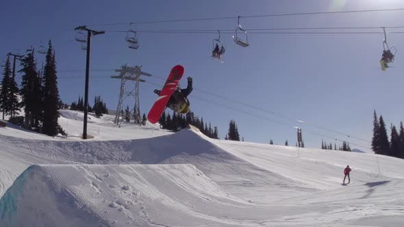 Thumbnail for A young man snowboarder going off jumps in a terrain park.