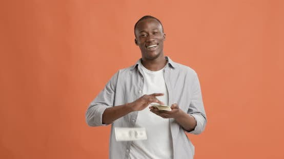 Rich Black Man Throwing Money and Laughing on Orange Background