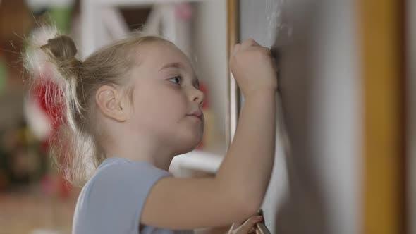 Seitenansicht eines genialen kleinen Mädchens, das mit Kreide auf Tafel im Klassenzimmer schreibt