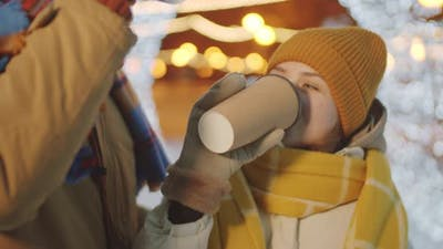 Romantic Couple Drinking Coffee and Kissing on Street with Xmas Lights