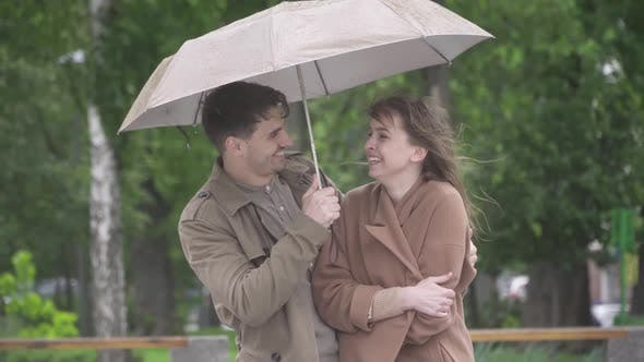 Thumbnail for Portrait of Positive Caucasian Handsome Man Smiling and Hugging Loving Girlfriend on Rainy Day