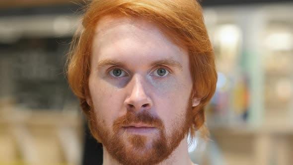Thumbnail for Serious Redhead Beard Man Looking at Camera