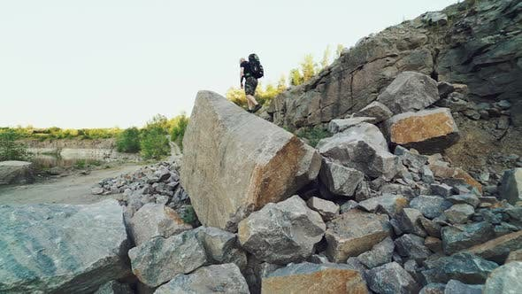 A traveler in shorts and with a backpack climbs onto a huge stone and sits on it amid a quarry