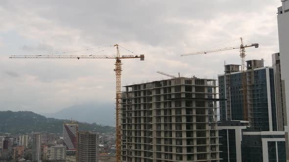 Thumbnail for Building Construction. Tower Crane on a Construction Site Lifts a Load at High-rise Building