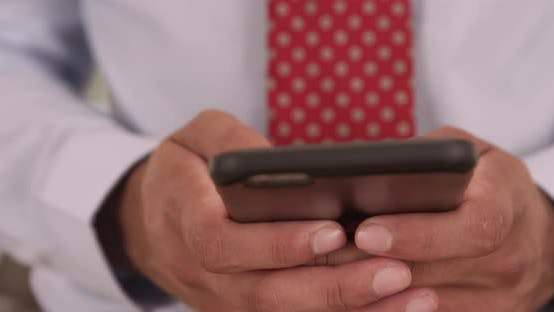 Thumbnail for Close up of man with tie sms texting on smartphone