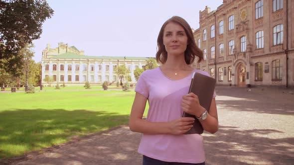 Thumbnail for Caucasian Woman with Computer Walks Near University