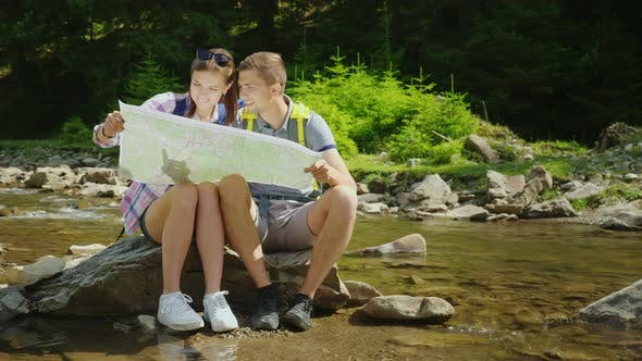 Cover Image for A Young Couple of Tourists Are Studying Together a Map. They Sit in a Picturesque Place Near a