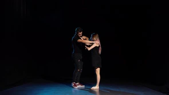 Romantic Choreography Against Black Background in Spotlight at Studio.