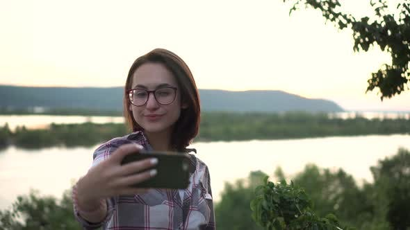 Thumbnail for A Young Woman Stands on a Hill Against the Background of the River and Mountains and Takes Pictures