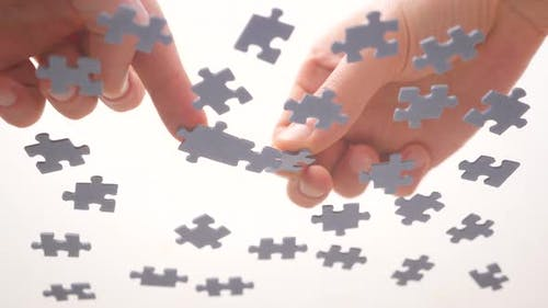 Assembling Jigsaw Puzzle. Pieces of a Jigsaw Puzzle Interconnecting By Male Hand. Fast Learning