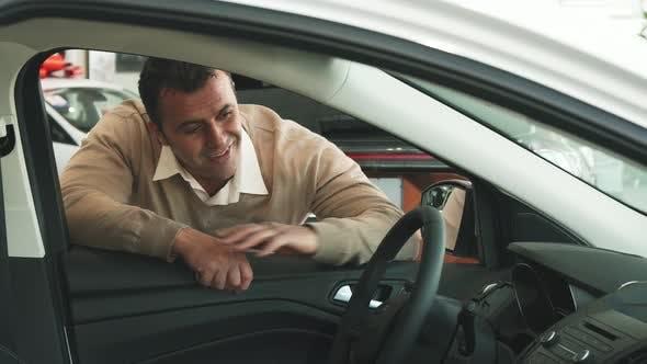 Thumbnail for An Adult Man Enjoys the Interior of a Car