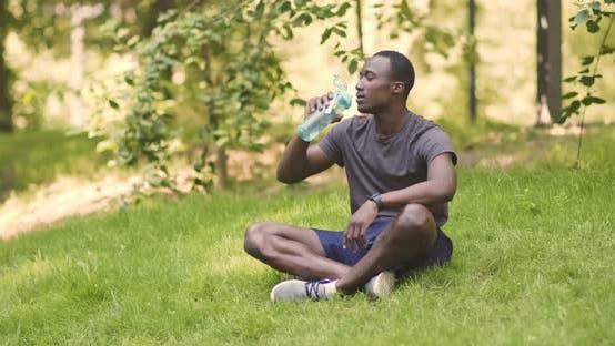 Thumbnail for Junge Afroamerikaner Kerl Trinkwasser aus Sportflasche