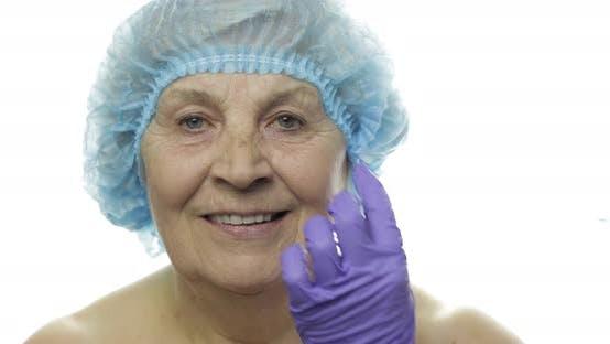 Thumbnail for Ältere Frau in Schutzhut. Arzt machen Gesichtsinjektionen für Patienten