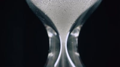 Glowing Sand Pours Down in Traditional Hourglass on Black