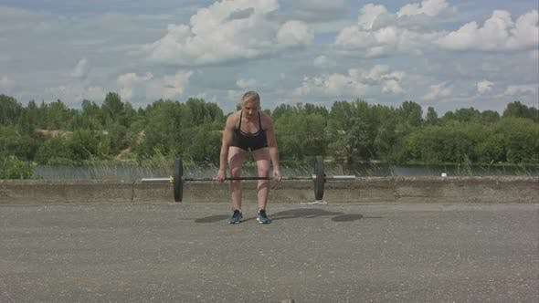 Thumbnail for Sporty Woman Exercising with Barbell Over City Waterside Background
