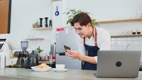 Asian Barista male use laptop computer enjoy doing digital marketing in cafe restaurant.