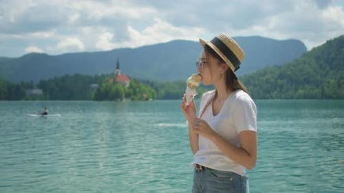 Young Woman is Eating Ice Cream on Shore of Lake Bled in Slovenia