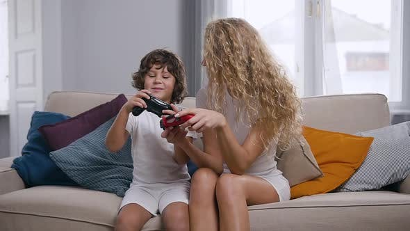 Thumbnail for Joyful Mother and Active Nice Little Boy Sitting on Soft Couch and Using Joysticks