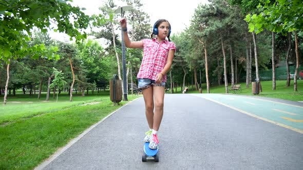 Thumbnail for Young Girl with Headphones on Skates in the Park