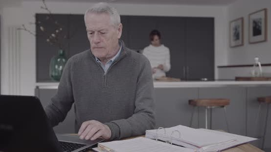 Senior adult male doing domestic finance on laptop at kitchen table, day in life