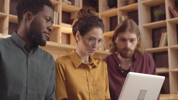 Thumbnail for Three Multiethnic Creative Colleagues Using Laptop in Coworking