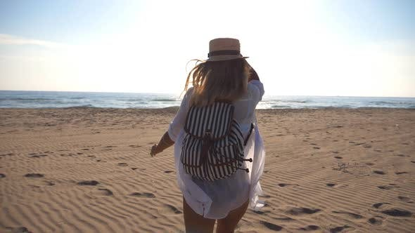 Thumbnail for Happy Girl in Bikini and Shirt with Backpack Running on the Beach To the Sea. Beautiful Woman
