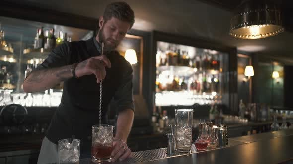 Thumbnail for Attractive Bearded Bartender Mixing Rum and Ice in the Glass with Long Metal Stick