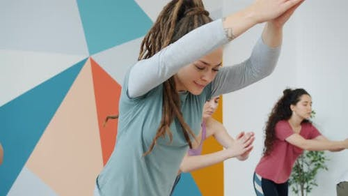 Cute Girl Doing Yoga with Group of People Practising Balance Asanas Busy with Practice